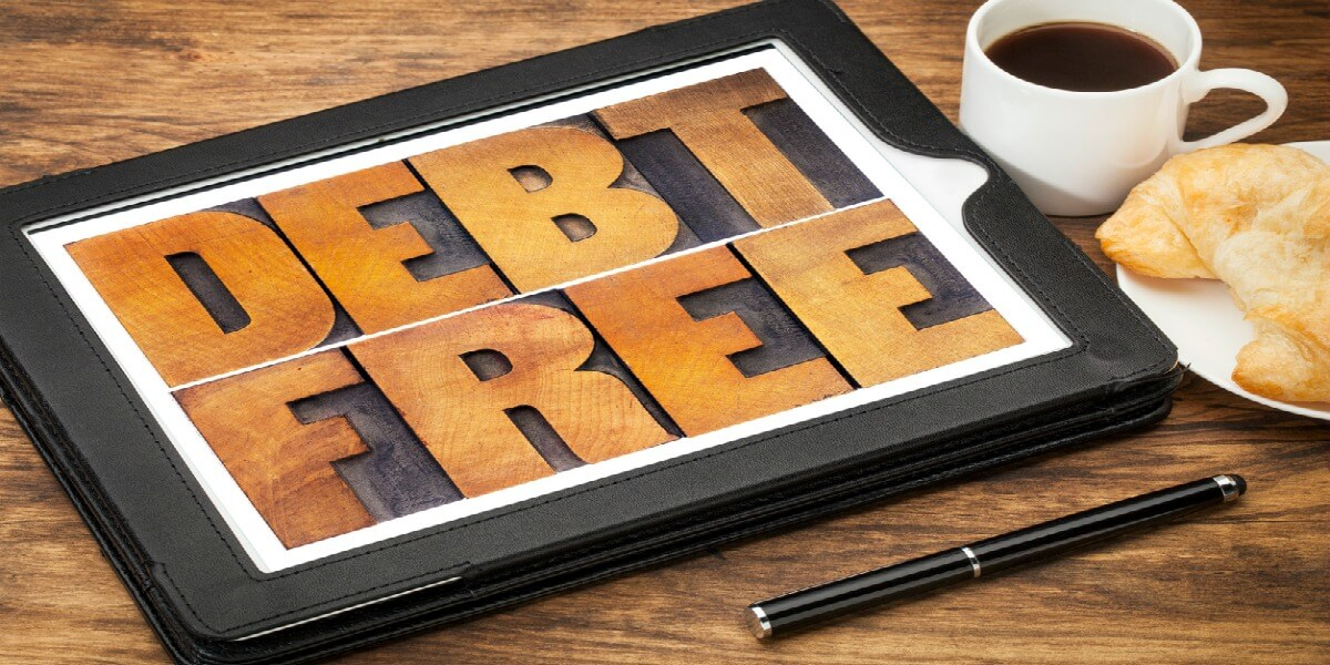 debt free concept - text in vintage letterpress wood type on a digital tablet with coffee and pastry