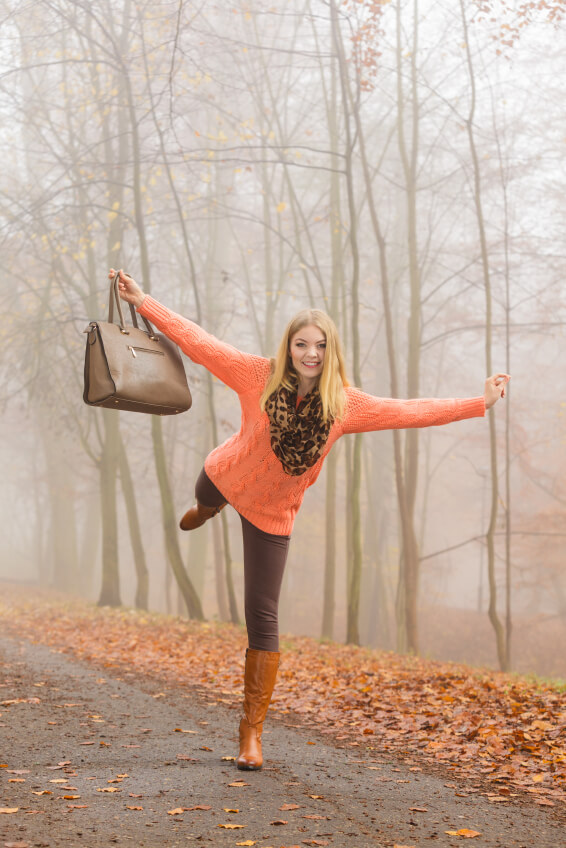 Carefree happy fashionable woman walking in foggy autumn park having fun. Pretty joyful young girl in sweater pullover with handbag relaxing in forest. Fall fashion vogue. Happiness.