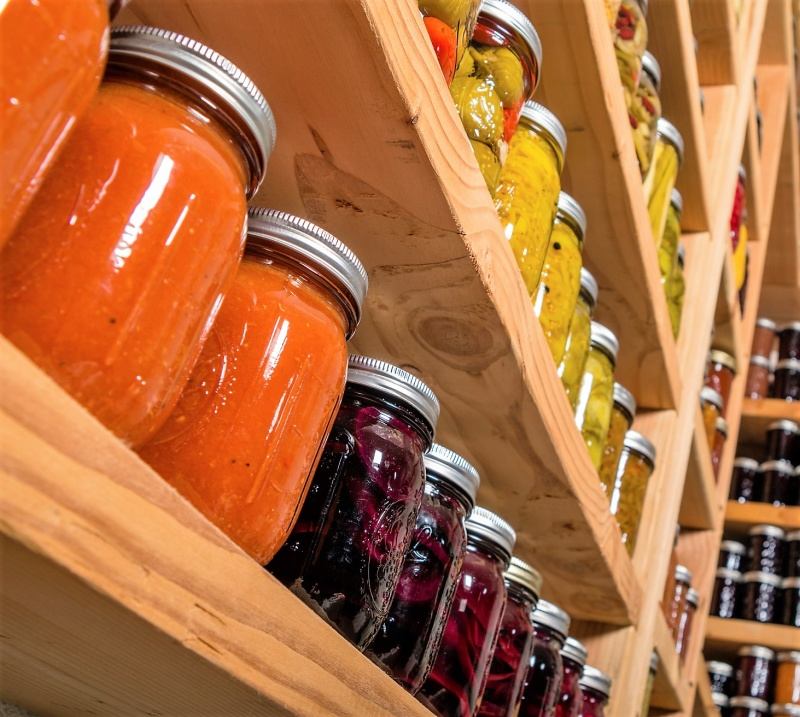 Canned goods on wooden storage shelves in pantry
