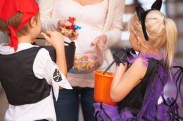 A little boy and girl receiving sweets from a neighbor