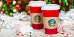 DALLAS, TX - NOVEMBER 19, 2015: A cup of Starbucks popular holiday beverage, served in the new 2015 designed red holiday cup. Displayed with candy canes against sparkly holiday background.