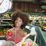 African American woman weighing bell peppers on scale at supermarket